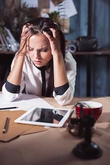 Jonge gefrustreerde vrouw die op zolder of op kantoor werkt voor een laptop die lijdt aan chronische dagelijkse hoofdpijn