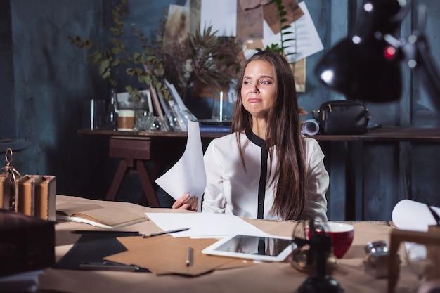 Jonge gefrustreerde vrouw die op zolder thuis of op bureau voor laptop werkt die aan chronische dagelijkse hoofdpijn lijdt