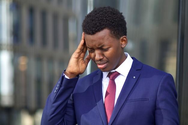 Jonge gefrustreerde wanhopige zakenman huilt, lijdt aan hoofdpijn, migraine. zwarte afrikaanse afro-amerikaanse man in formeel pak raakt zijn hoofd, tempel vanwege pijn. wanhoop, mislukking