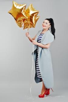 Jonge geglimlachte vrouw met gouden ballonnen