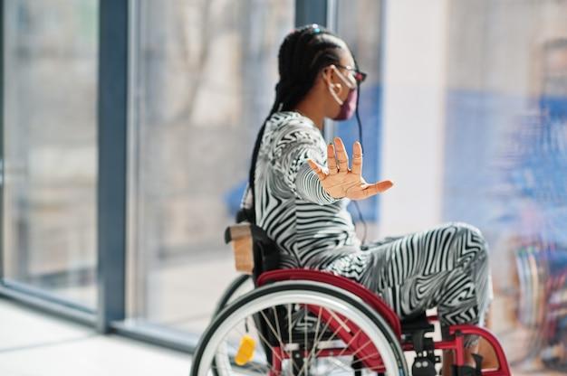 Jonge gehandicapte afro-amerikaanse vrouw in rolstoel thuis, draag gezichtsmasker stopbord met de hand.