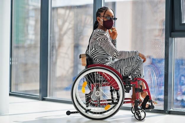 Jonge gehandicapte afro-amerikaanse vrouw in rolstoel thuis, draag gezichtsmasker.