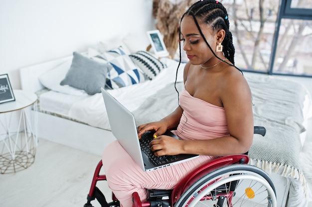 Jonge gehandicapte afro-amerikaanse vrouw in rolstoel thuis werken met laptop.