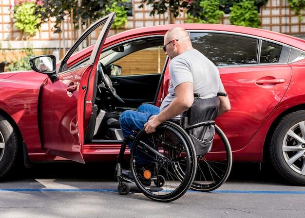 Jonge gehandicapte bestuurder die in rode auto fom rolstoel krijgt