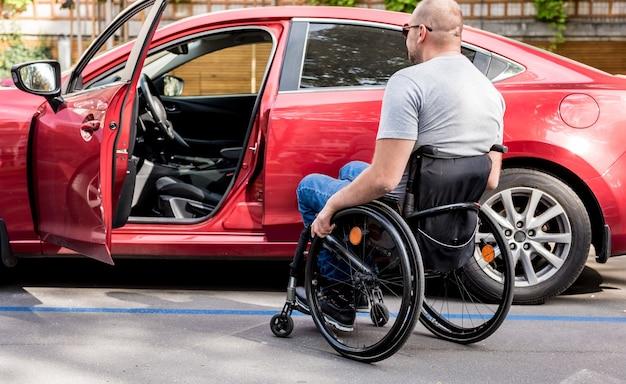 Jonge gehandicapte bestuurder die in rode auto van rolstoel krijgt.