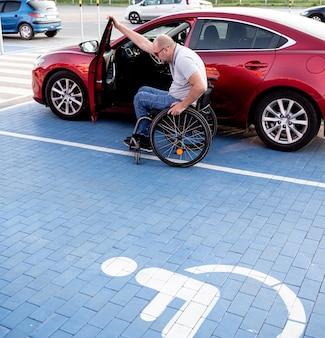 Jonge gehandicapte bestuurder stapt in rode auto uit rolstoel