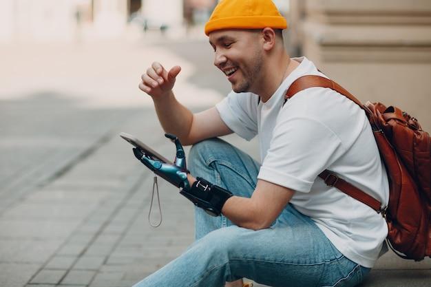 Jonge gehandicapte man met behulp van mobiele telefoon met kunstmatige prothese hand in vrijetijdskleding buitenshuis