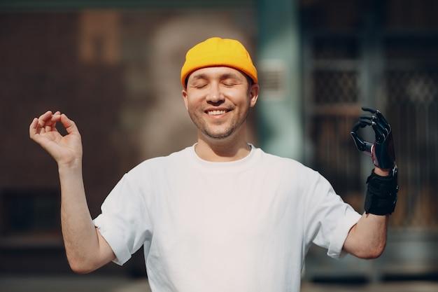 Jonge gehandicapte man met kunstmatige prothese hand ok gebaar mudra mediteren op straat buiten in de stad
