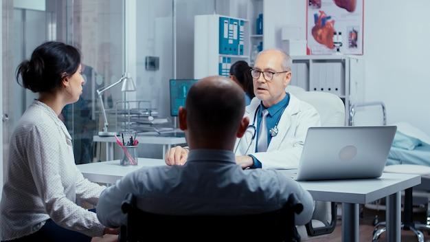 Jonge gehandicapte man naar dokterspraktijk naast zijn vrouw. dsabled handicap gehandicapte behandeling in moderne privé ziekenhuis of kliniek. geneeskunde en gezondheidszorgsysteem