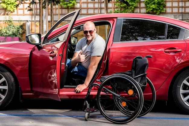 Jonge gehandicapte man op de bestuurdersstoel van zijn auto.