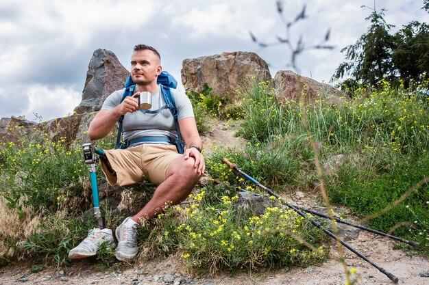 Jonge gehandicapte mannelijke toerist die thee drinkt terwijl hij een toeristische route in de wilde natuur heeft