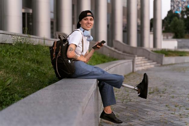 Jonge gehandicapte persoon met beenprothese buitenshuis