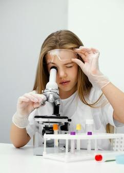 Jonge geïntrigeerde meisjeswetenschapper die microscoop gebruikt