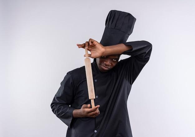 Jonge geïrriteerde afro-amerikaanse kok in uniform chef houdt deegroller en kijkt naar camera op wit met kopie ruimte