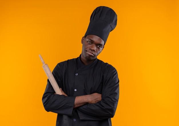 Jonge geïrriteerde afro-amerikaanse kok in uniform chef houdt deegroller met gekruiste armen op oranje met kopie ruimte