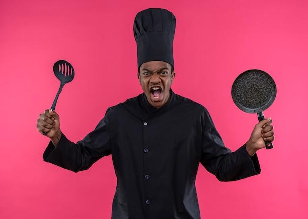 Jonge geïrriteerde afro-amerikaanse kok in uniform chef houdt koekenpan en spatel geïsoleerd op roze achtergrond met kopie ruimte