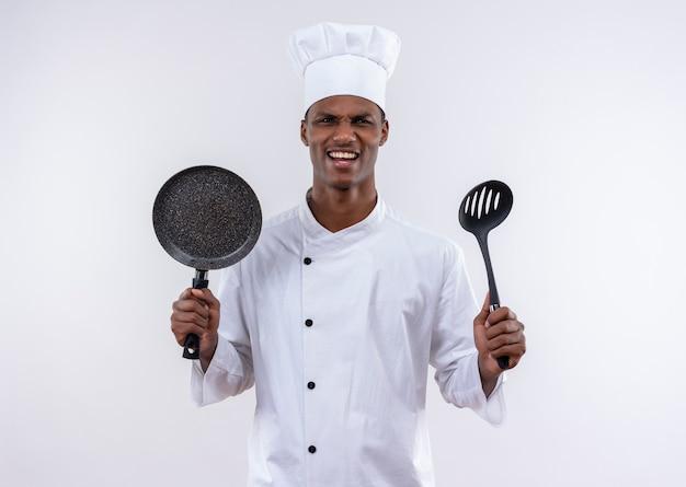 Jonge geïrriteerde afro-amerikaanse kok in uniform chef houdt koekenpan en spatel op geïsoleerde witte achtergrond met kopie ruimte