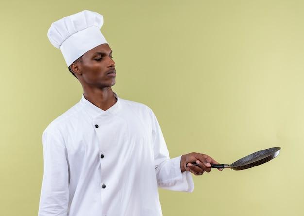 Jonge geïrriteerde afro-amerikaanse kok in uniform chef-kok houdt en kijkt naar koekenpan geïsoleerd op groene achtergrond met kopie ruimte