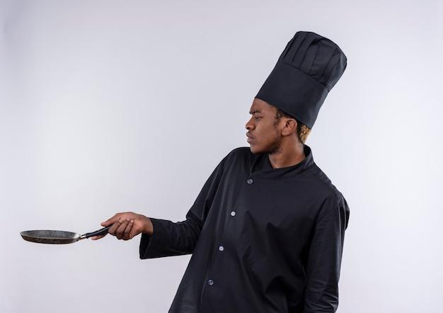 Jonge geïrriteerde afro-amerikaanse kok in uniform chef staat zijwaarts en houdt koekenpan geïsoleerd op een witte achtergrond met kopie ruimte