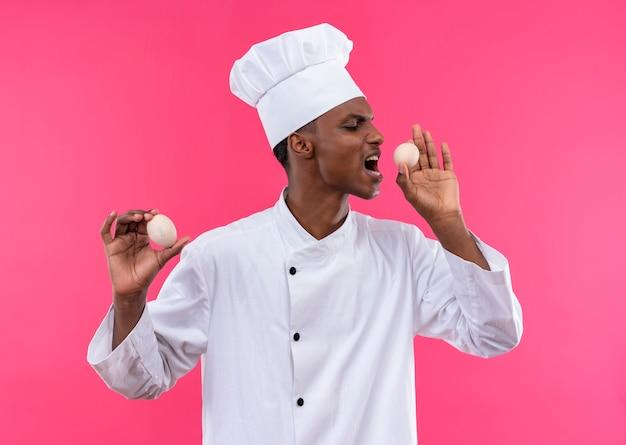 Jonge geïrriteerde afro-amerikaanse kok in uniform van de chef houdt eieren in beide handen en kijkt naar de zijkant geïsoleerd op roze achtergrond met kopie ruimte