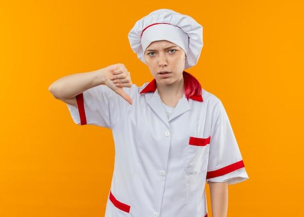 Jonge geïrriteerde blonde vrouwelijke chef-kok in eenvormige chef-kok die duimen neer op oranje muur wordt geïsoleerd