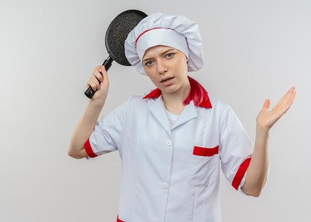 Jonge geïrriteerde blonde vrouwelijke chef-kok in uniform chef houdt koekenpan en kijkt geïsoleerd op een witte muur