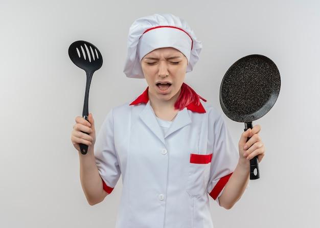 Jonge geïrriteerde blonde vrouwelijke chef-kok in uniform chef houdt koekenpan en spatel geïsoleerd op een witte muur