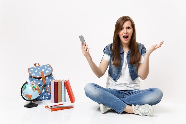 Jonge, geïrriteerde, boze vrouw die een mobiele telefoon vasthoudt en de hand schreeuwt terwijl hij in de buurt van de wereldbol, rugzak, schoolboeken geïsoleerd zit