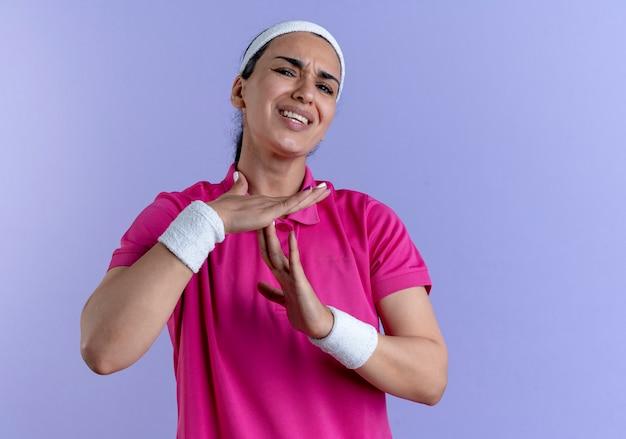Jonge geïrriteerde kaukasische sportieve vrouw die hoofdband en polsbandjes draagt gebaren time-out handteken op paars met kopie ruimte