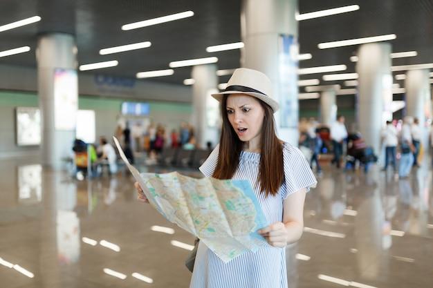 Jonge geïrriteerde ontevreden reizigerstoeristenvrouw houdt papieren kaart vast, zoekt route, wacht in lobbyhal op internationale luchthaven