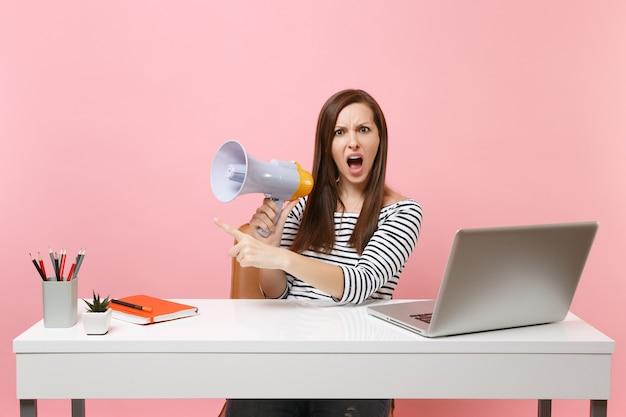 Jonge geïrriteerde verontwaardigde vrouw schreeuwen in megafoon wijzende wijsvinger zitten werk aan witte bureau met pc-laptop geïsoleerd op pastel roze achtergrond. prestatie zakelijke carrière concept. ruimte kopiëren.