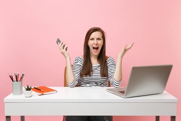 Jonge geïrriteerde vrouw die handen uitspreidt terwijl ze een mobiele telefoon vasthoudt terwijl ze op kantoor werkt met een pc-laptop