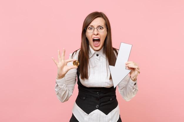 Jonge geïrriteerde zakenvrouw in glazen schreeuwende houd bitcoin, neerwaartse valpijl geïsoleerd op pastelroze achtergrond. dame baas. prestatie carrière rijkdom concept. kopieer ruimte voor advertentie.