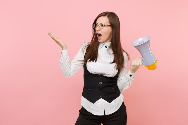 Jonge geïrriteerde zakenvrouw in pak, bril met megafoon spreidende handen opzij kijkend geïsoleerd op roze achtergrond. dame baas. prestatie carrière rijkdom concept. kopieer ruimte voor advertentie.
