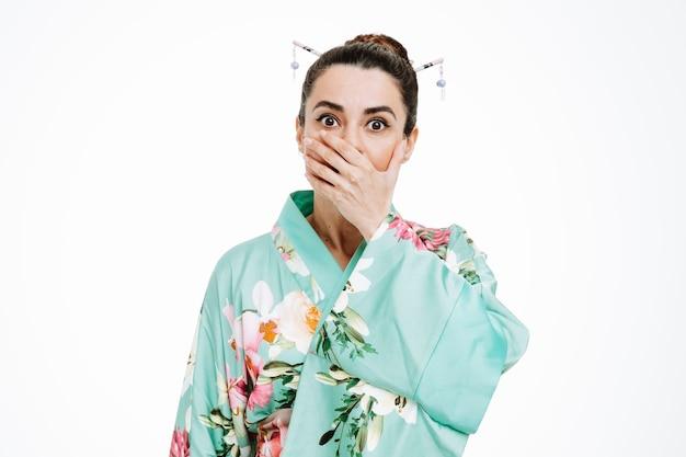 Jonge geisha-vrouw in traditionele japanse kimono die naar de voorkant kijkt en geschokt is die de mond bedekt met de hand die over een witte muur staat