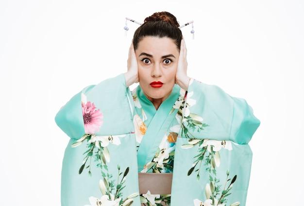 Jonge geisha-vrouw in traditionele japanse kimono die naar de voorkant kijkt en gestrest en geschokt is die oren bedekt met handen die over een witte muur staan
