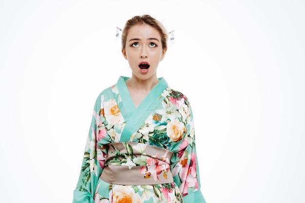 Jonge geisha-vrouw in traditionele japanse kimono die opkijkt, geschokt en verbaasd met wijd open mond over een witte muur