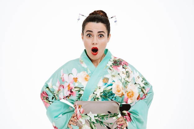 Jonge geisha vrouw in traditionele japanse kimono kijkend naar de voorkant met wijd open mond en ogen verbaasd en verrast staande over witte muur
