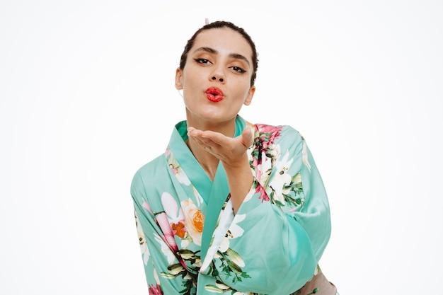 Jonge geishavrouw in traditionele japanse kimono gelukkig en positief die een kus op wit blaast