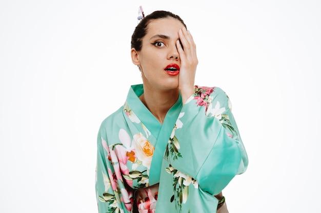 Jonge geishavrouw in traditionele japanse kimono verbaasd en verrast die één oog bedekt met de hand op wit