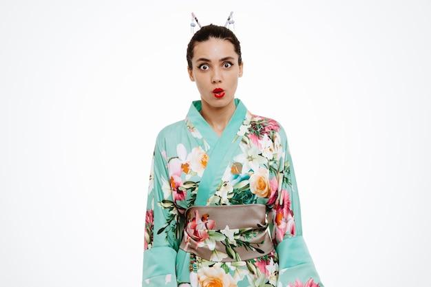 Jonge geishavrouw in traditionele japanse kimono verbaasd en verrast op wit