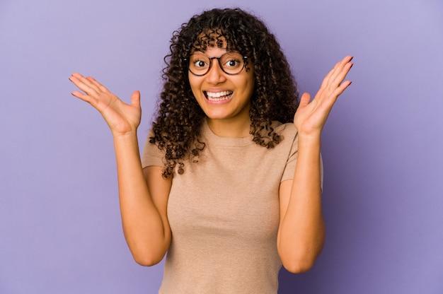 Jonge geïsoleerde afrovrouw die een aangename opgewonden verrassing ontvangt en handen opheft