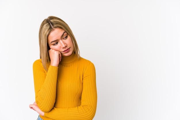 Jonge geïsoleerde blonde kaukasische vrouw die droevig en peinzend voelt, bekijkend exemplaarruimte.