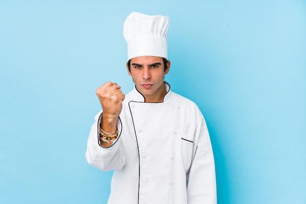 Jonge geïsoleerde kokmens toont vuist aan camera, agressieve gezichtsuitdrukking.