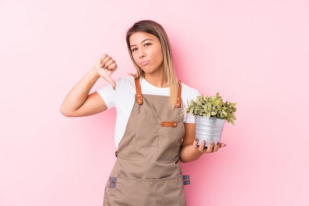 Jonge geïsoleerde tuinman kaukasische vrouw tonend een afkeergebaar, duimen. meningsverschil concept.