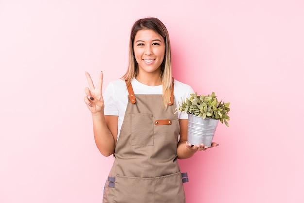 Jonge geïsoleerde tuinman kaukasische vrouw tonend nummer twee met vingers.