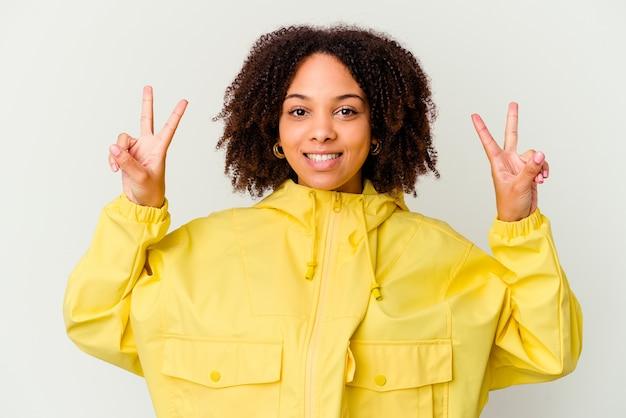 Jonge geïsoleerde vrouw die overwinningsteken toont en breed glimlacht