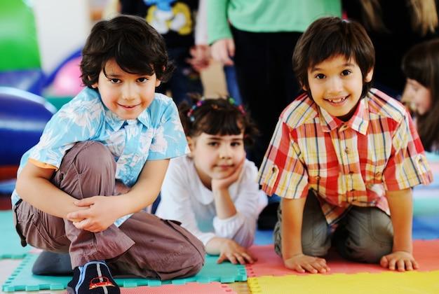 Jonge geitjes die op kleurrijke kleuterschoolspeelplaats spelen