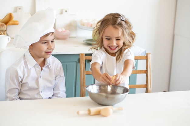 Jonge geitjes in witte chef-kok eenvormig voorbereidend voedsel op de keuken