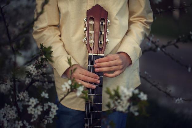 Jonge geitjeshanden die gitaar op aardachtergrond houden.